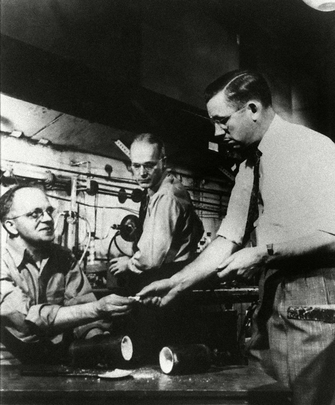 Dr. Roy J. Plunkett, right, holder of the original patent for Teflon, poses with his product and DuPont chemists re-enact the making of the product in one of the company's laboratory. Photo: AP/Shutterstock (6650656a)